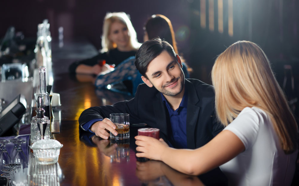 Man approaching a woman at a bar