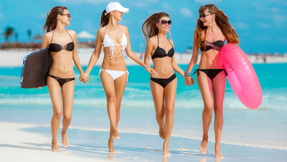 Women in bikinis frolicking along the beach